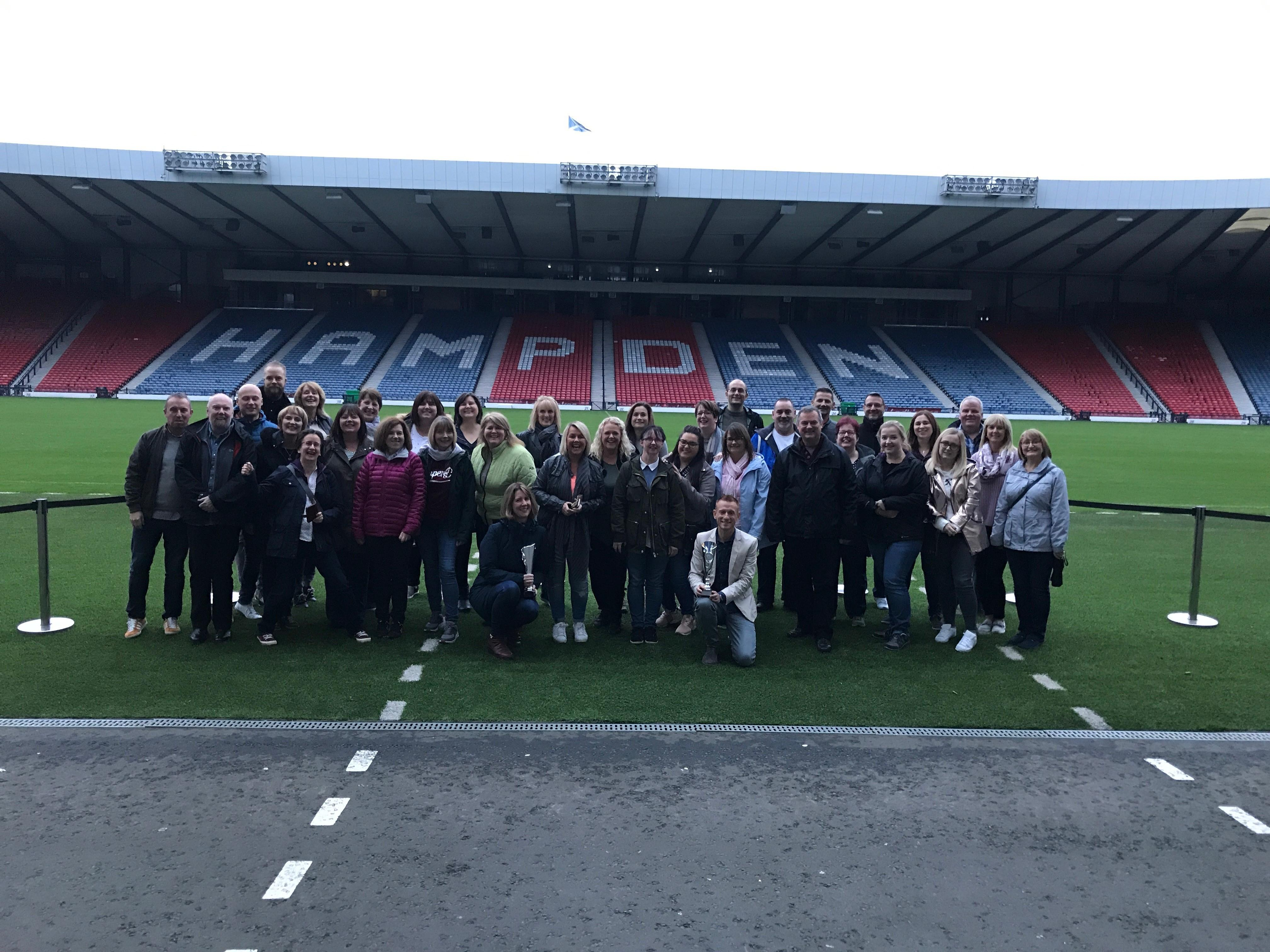 Staff team pitchside at Hampden Stadium